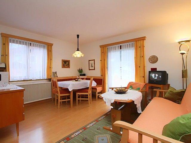 Gemütliches Wohnzimmer mit Couch, Sitzecke und TV